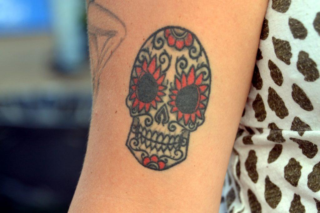 Tatuaje con calavera y detalles en rojo