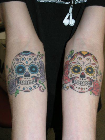 Dos tatuajes de calaveras en los brazos