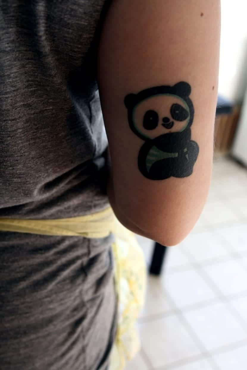 tatuaje de oso panda encima codo