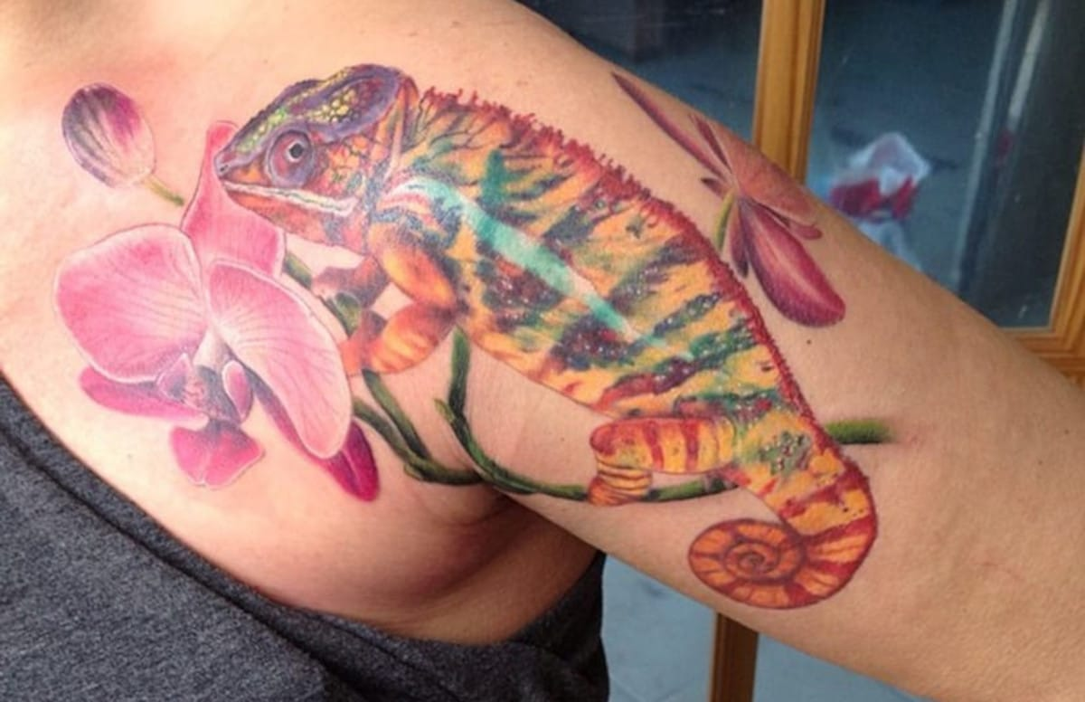 Camaleón en el hombro con orquídea