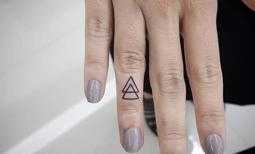 Tatuajes de triángulos en los dedos de las manos
