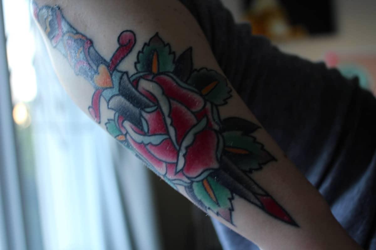 Tatuaje tradicional en el brazo con rosa y daha