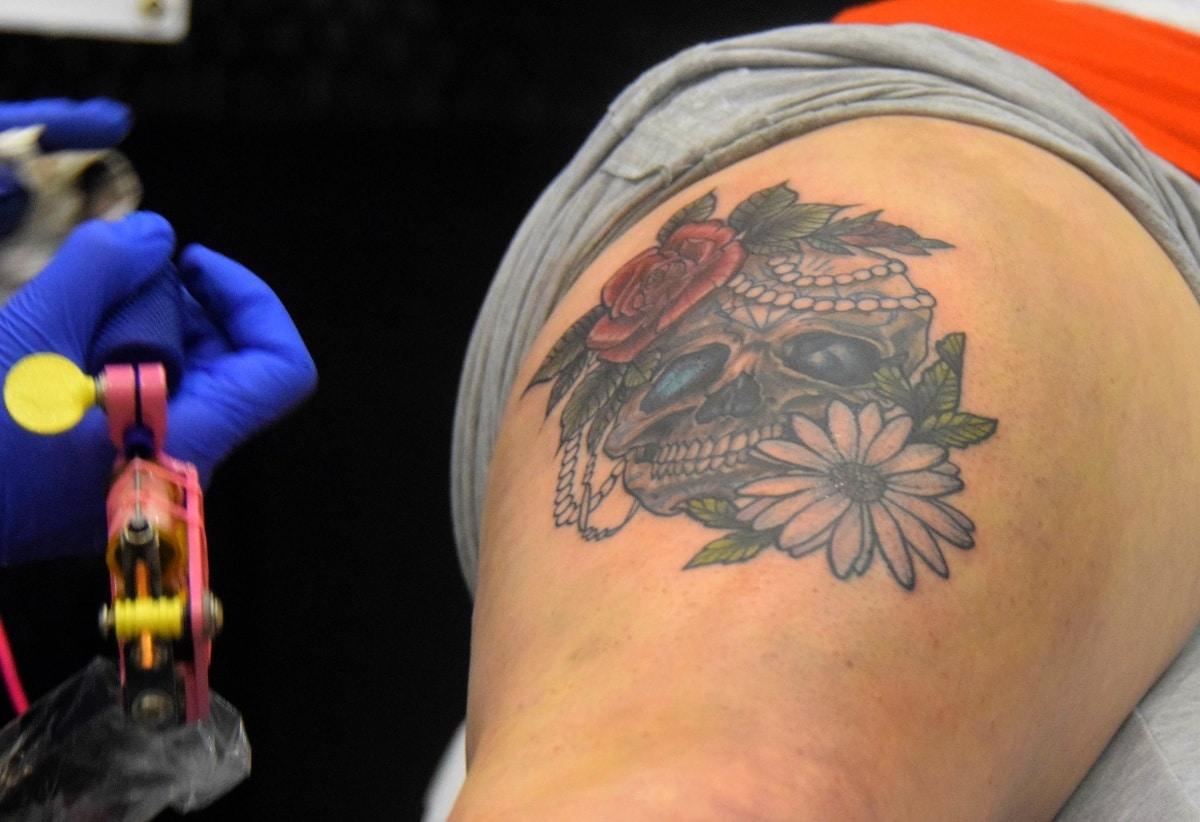 Tatuaje de calavera con margarita y rosa para dar un giro original