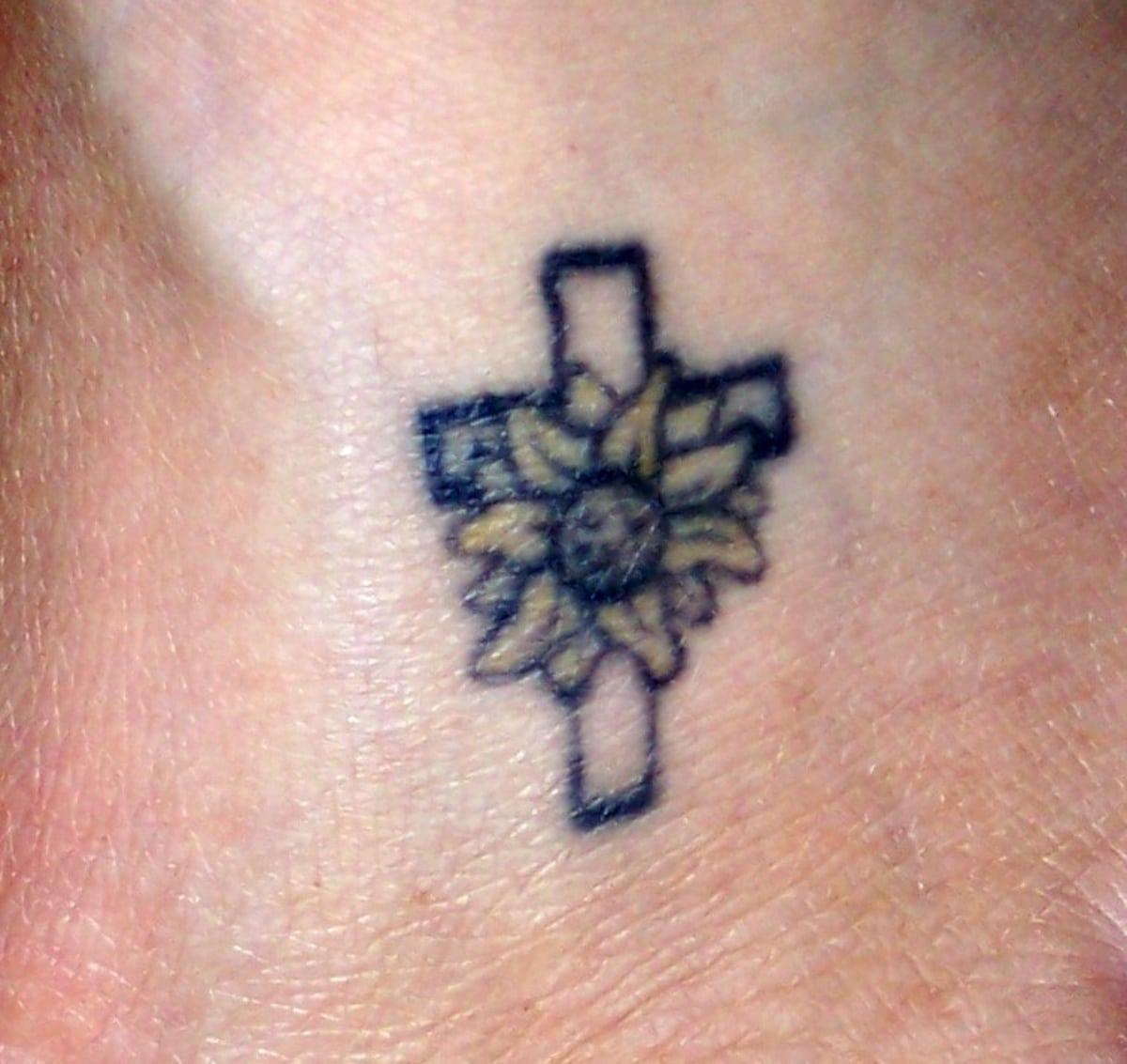 Expresa tu fe con un tatuaje de margarita y cruz