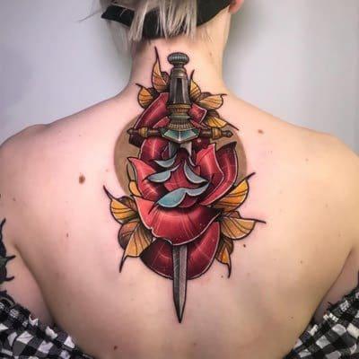 Impresionante tatuaje de daga y rosa en la espalda