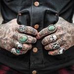 Manos tatuadas con el pulgar en los bolsillos