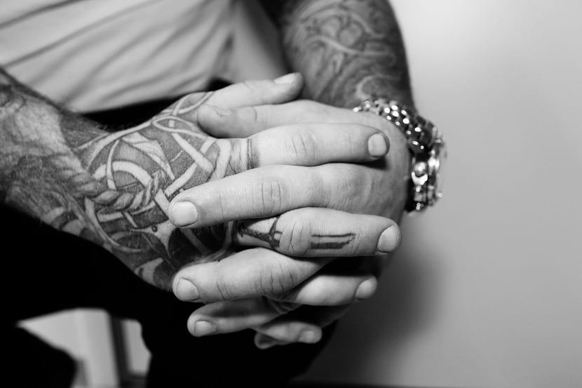 Manos tatuadas con los dedos entrelazados