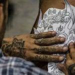 Hombre con las manos tatuadas tatuando