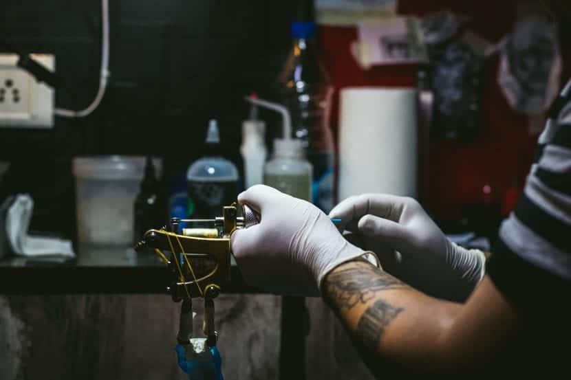 Tatuador preparando máquina