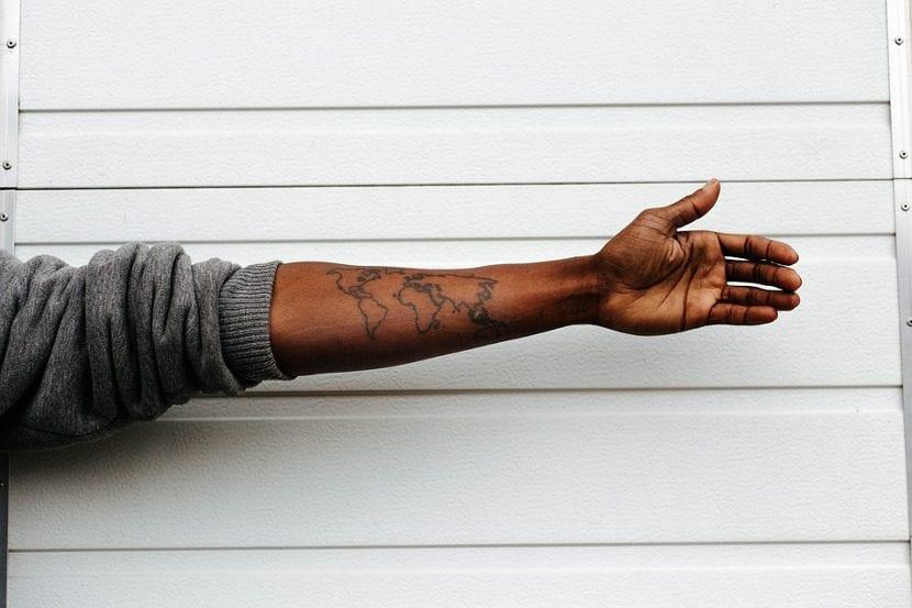 Brazo tatuado mapa mundo