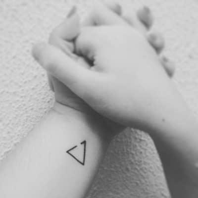 Pequeño tatuaje de triángulo abierto o delta